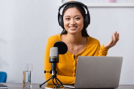 excited asian radio host in wireless headphones looking at camera while sitting near microphone and laptop