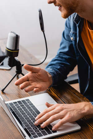 partial view of broadcaster talking in microphone and gesturing while using laptop at workplace Stock Photo