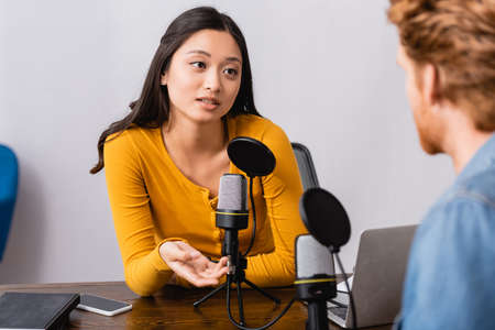 selective focus of brunette asian radio host gesturing while interviewing man in studio