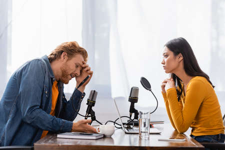 young asian radio host looking at tense man touching head during interview in studio