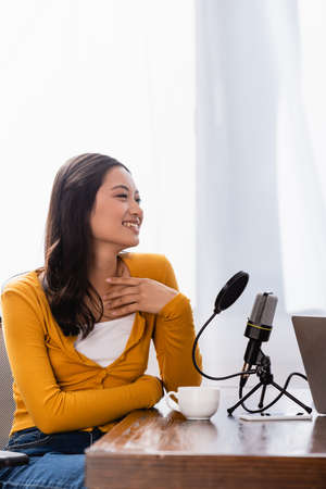excited asian broadcaster touching chest while sitting near microphone at workplace Stock Photo