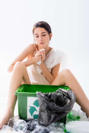 selective focus of brunette woman sitting near plastic bags and trash bin with recycle sign on white, ecology concept Banque d'images