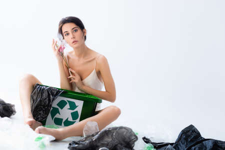 selective focus of barefoot woman holding flower in wrap near plastic bags and trash can with recycle sign on white, ecology concept Banque d'images