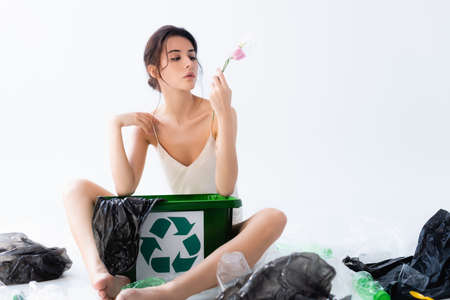 selective focus of young woman holding flower in wrap near plastic bags and trash can with recycle sign on white, ecology concept