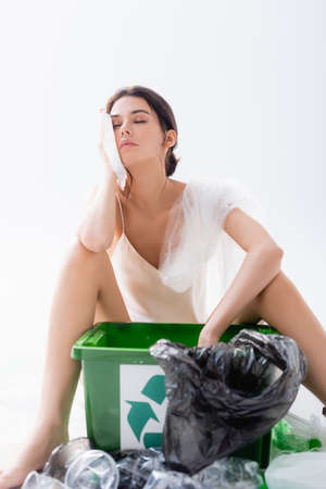 selective focus of woman with closed eyes in silk dress sitting near plastic bags and trash bin with recycle sign on white, ecology concept Banque d'images