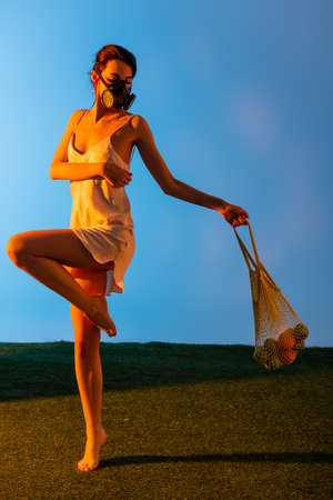 barefoot woman in gas mask posing while holding reusable string bag with fruits on blue