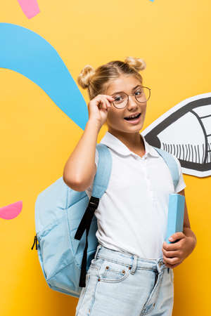 excited schoolchild touching eyeglasses and looking at camera while holding book near colorful elements and paper pencil on yellow Banque d'images