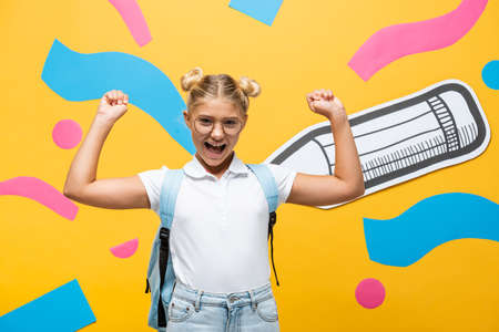 excited schoolgirl in eyeglasses showing winner gesture near paper pencil and multicolored elements on yellow Reklamní fotografie