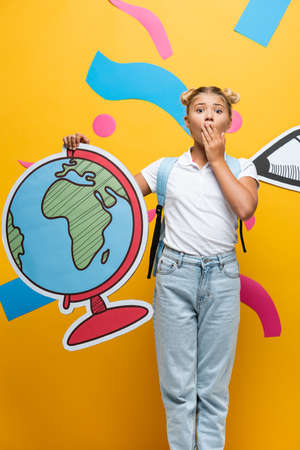shocked schoolgirl covering mouth with hand while holding globe maquette near paper pencil and decorative elements on yellow