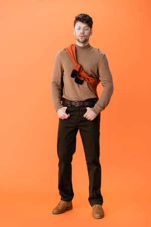 full length of stylish man in glasses standing with hands in pockets on orange Stock fotó - 155452163