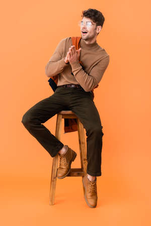 stylish man in autumn outfit and glasses sitting with praying hands on wooden stool on orange Stock fotó