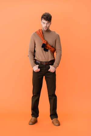 stylish man in glasses and autumn outfit standing with hands in pockets on orange Stock fotó - 155452224