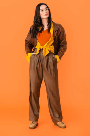 full length of young woman in autumn outfit standing with hands in pockets on orange Stock fotó
