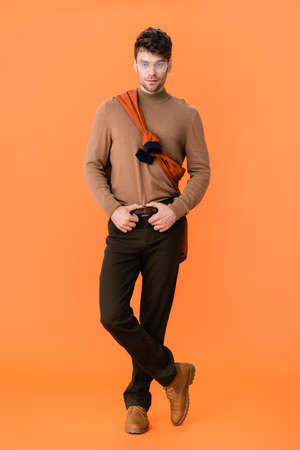 trendy man in autumn outfit and glasses standing with crossed legs on orange