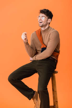 excited man in autumn outfit and glasses sitting on wooden stool and laughing on orange Stock fotó - 155452252