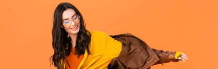 panoramic shot of stylish woman in glasses and leather jacket isolated on orange