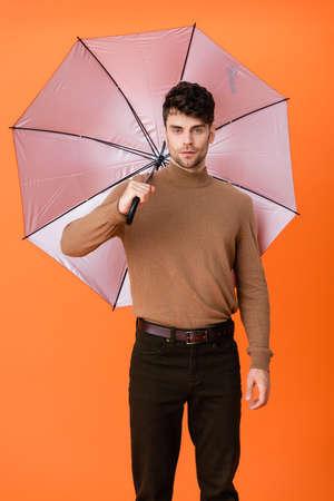 stylish man in autumn outfit standing under umbrella on orange Stock fotó - 155452259
