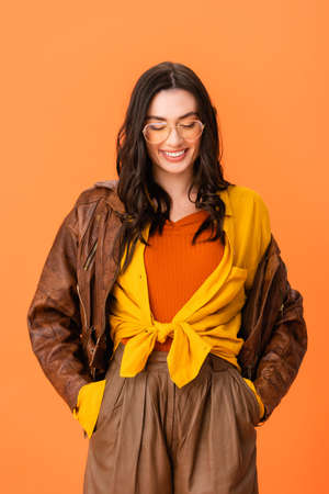 young woman in autumn outfit standing with hands in pockets and looking down isolated on orange Stock fotó - 155452260