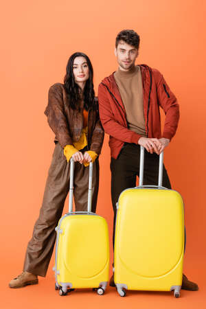 full length of fashionable couple in autumn outfit standing with yellow baggage on orange
