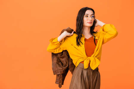 trendy woman in glasses and autumn outfit holding leather jacket while standing isolated on orange Stock fotó - 155452276