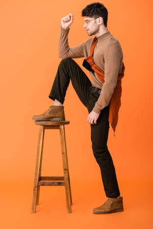 side view of stylish man in autumn outfit and glasses standing with leg on wooden stool on orange