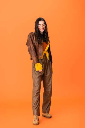 full length of young woman in autumn outfit and glasses standing on orange Stock fotó