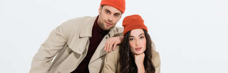 panoramic concept of trendy man in beanie hat leaning on brunette woman isolated on white Stock Photo