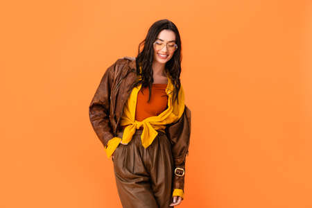 young woman in autumn outfit standing with hand in pocket and looking down isolated on orange Stock fotó - 155452285