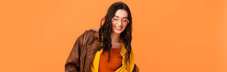 panoramic concept of young woman in autumn outfit looking down isolated on orange Stock Photo