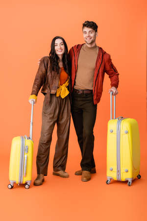 full length of stylish couple in autumn outfit standing near yellow baggage on orange Stock fotó - 155452305