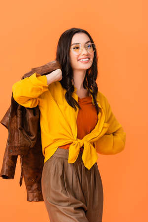 trendy woman in glasses and autumn outfit holding leather jacket while standing with hand on hip isolated on orange