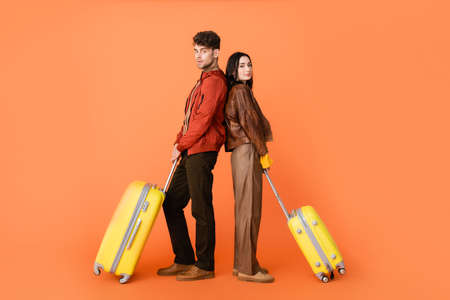 full length of trendy couple in autumn outfit standing back to back with yellow baggage on orange Stock fotó - 155452323