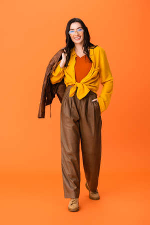full length of joyful woman in autumn outfit holding leather jacket and standing with hand in pocket on orange Stock fotó