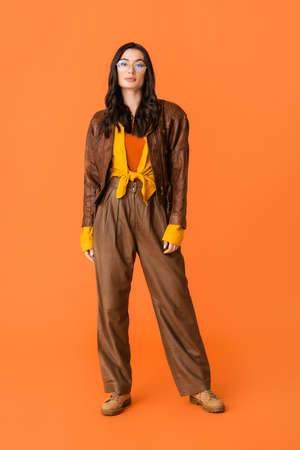 full length of stylish woman in autumn outfit and glasses standing on orange Stock fotó - 155452340