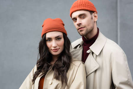 fashionable couple in trench coats and hats standing near gray wall outside