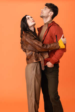 brunette woman hugging stylish man standing with hand in pocket and looking up on orange