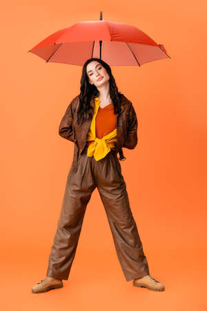 full length of young fashionable woman in autumn outfit and boots standing with umbrella on orange Stock fotó