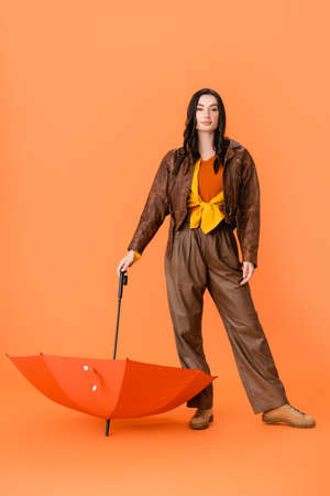 full length of fashionable woman in autumn outfit and boots standing with umbrella on orange Stock fotó - 155452399