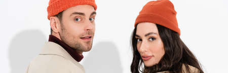 panoramic concept of trendy couple in beanie hats looking at camera on white Stock Photo