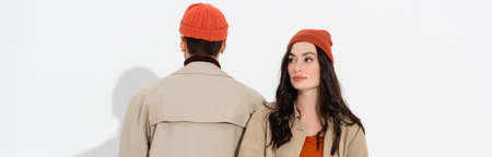panoramic concept of stylish woman sitting near man in beanie hat on white Stock Photo
