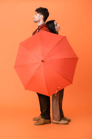full length of fashionable couple in autumn outfit and boots standing with umbrella on orange Stock fotó - 155452411