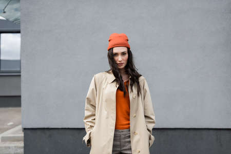 stylish woman in trench coat and beanie hat standing with hands in pockets near building Stock fotó - 155452422