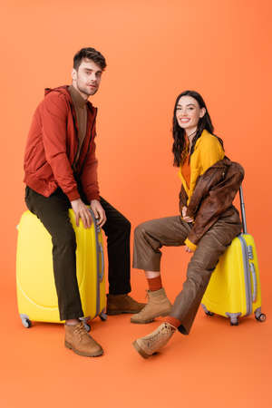 joyful and trendy couple in autumn outfit sitting on yellow baggage on orange