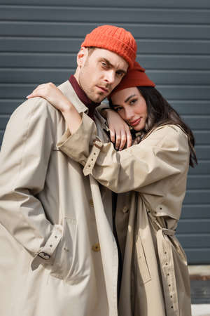 trendy woman in trench coat and hat hugging man standing with hand in pocket