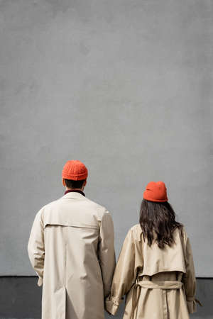 back view of couple in trench coats and hats standing near gray wall Stock fotó - 155452476