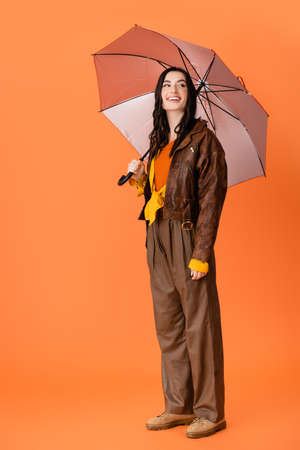 full length of joyful woman in autumn outfit and boots standing with umbrella on orange