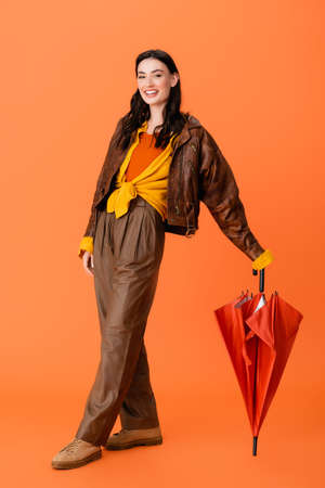 full length of woman in autumn outfit and boots standing with umbrella on orange Stock fotó