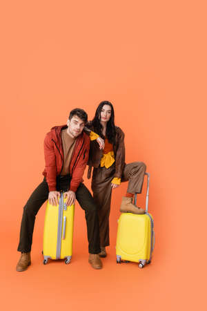 full length of trendy couple in autumn outfit sitting yellow baggage on orange Stock Photo