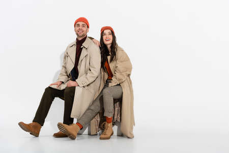 brunette woman in trench coat looking up while sitting near trendy man in beanie hat on white