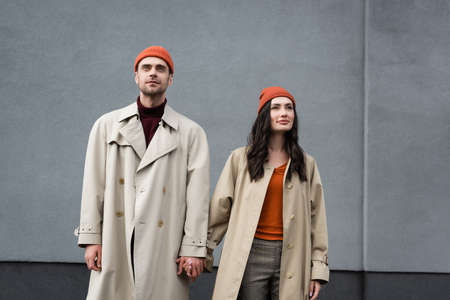 stylish couple in trench coats and hats standing and holding hands near gray wall outside